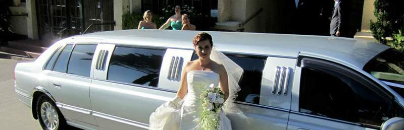 800 x 258 Wedding Bride standing next to Ford LTD super stretch wedding limo for hire